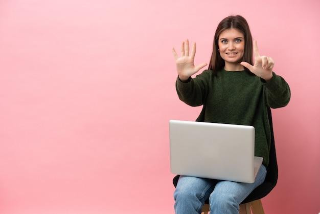 Młoda kaukaska kobieta siedzi na krześle z laptopem na białym tle na różowym tle, licząc siedem palcami