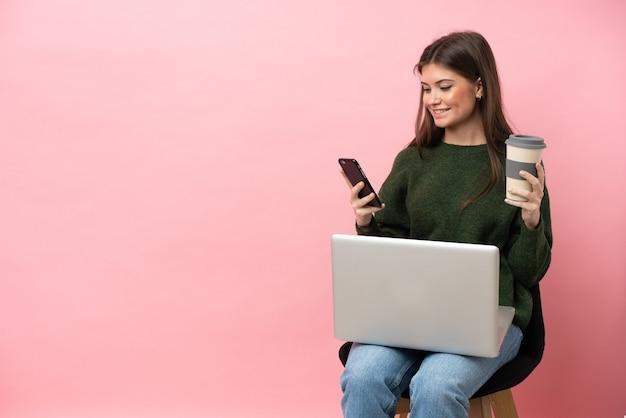 Młoda kaukaska kobieta siedzi na krześle z laptopem na białym tle na różowym tle, trzymając kawę na wynos i telefon komórkowy