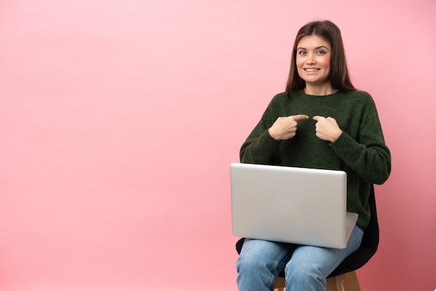 Młoda kaukaska kobieta siedzi na krześle z laptopem na białym tle na różowym tle z niespodzianką wyrazem twarzy