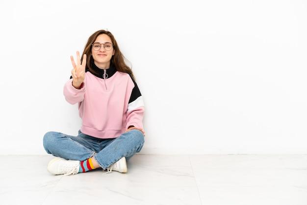 Młoda kaukaska kobieta siedzi na podłodze na białym tle szczęśliwa i liczy trzy palcami