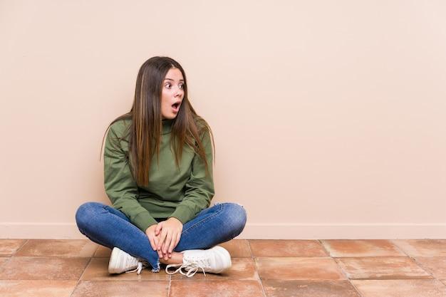 Młoda kaukaska kobieta siedzi na podłodze odizolowana, zszokowana czymś, co widziała.