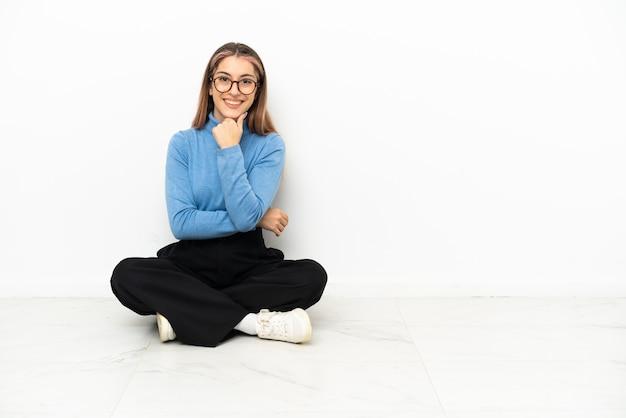 Młoda kaukaska kobieta siedzi na podłodze w okularach i uśmiecha się