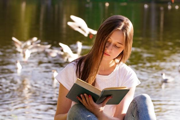 Młoda kaukaska kobieta siedzi nad brzegiem jeziora czyta książkę w słoneczny dzień czyta na świeżym powietrzu w parku
