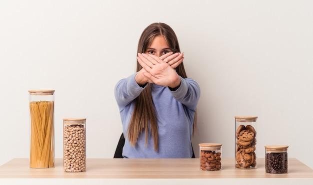 Młoda kaukaska kobieta siedzi przy stole z garnkiem na jedzenie na białym tle, wykonując gest odmowy