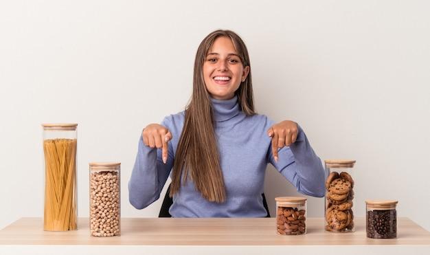 Młoda kaukaska kobieta siedzi przy stole z garnkiem żywności na białym tle wskazuje palcami w dół, pozytywne uczucie.