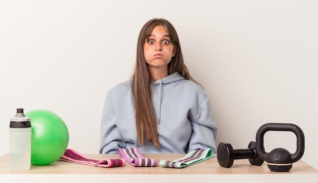 Młoda kaukaska kobieta siedzi przy stole ze sprzętem sportowym na białym tle dmucha w policzki, ma zmęczony wyraz twarzy. koncepcja wyraz twarzy.