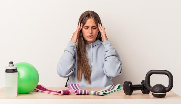 Młoda kaukaska kobieta siedzi przy stole ze sprzętem sportowym na białym tle dotyka świątyń i ma ból głowy.