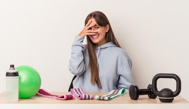 Młoda kaukaska kobieta siedzi przy stole ze sprzętem sportowym na białym tle mruga do kamery palcami, zakłopotana zakrywając twarz.