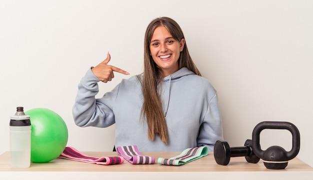 Młoda kaukaska kobieta siedzi przy stole ze sprzętem sportowym na białym tle osoba wskazująca ręcznie na miejsce na koszulkę, dumna i pewna siebie