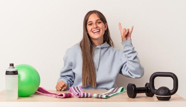 Młoda kaukaska kobieta siedzi przy stole ze sprzętem sportowym na białym tle pokazując gest rogów jako koncepcję rewolucji.