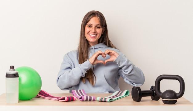 Młoda kaukaska kobieta siedzi przy stole ze sprzętem sportowym na białym tle, uśmiechając się i pokazując rękami kształt serca.