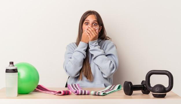 Młoda kaukaska kobieta siedzi przy stole ze sprzętem sportowym na białym tle w szoku obejmującym usta rękami.