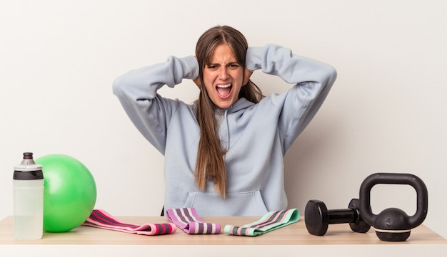 Młoda kaukaska kobieta siedzi przy stole ze sprzętem sportowym na białym tle zakrywając uszy rękami starając się nie słyszeć zbyt głośnego dźwięku.