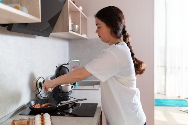Młoda kaukaska kobieta smaży jajka na śniadanie na kuchence indukcyjnej. widok z boku. koncepcja domowego posiłku