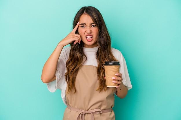 Młoda kaukaska kobieta sprzedawczyni w sklepie trzyma kawę na wynos na białym tle na niebieskim tle pokazując gest rozczarowania palcem wskazującym.