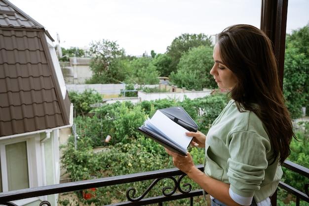 Młoda kaukaska kobieta stoi na balkonie z notatnikiem w ręku czyta zapisy