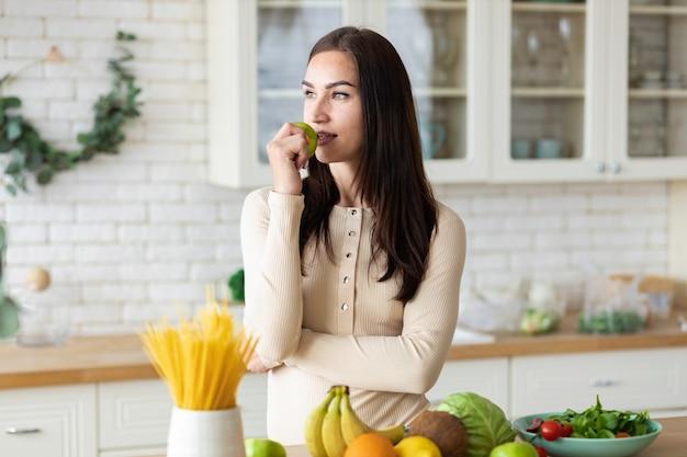 Młoda kaukaska kobieta stoi w kuchni z zielonym jabłkiem w dłoniach. zdrowy styl życia i koncepcja zdrowej żywności