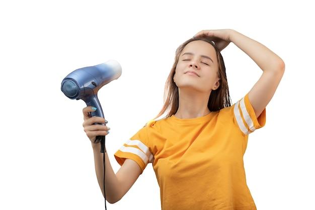 Młoda kaukaska kobieta suszy włosy suszarką na białym tle