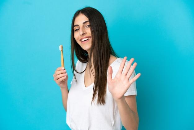 Młoda kaukaska kobieta szczotkuje zęby na białym tle na niebieskim tle, pozdrawiając ręką ze szczęśliwym wyrazem twarzy