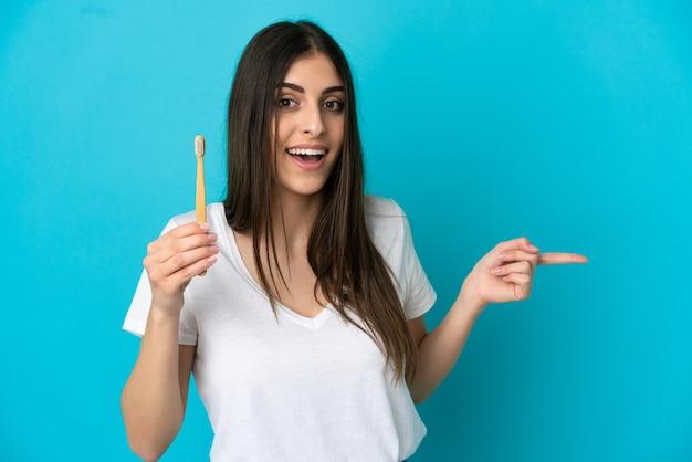 Młoda kaukaska kobieta szczotkuje zęby na białym tle na niebieskim tle zaskoczona i wskazująca palcem w bok