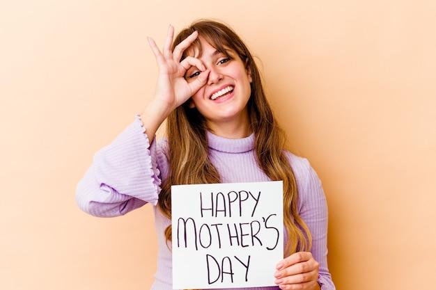 Młoda kaukaska kobieta trzyma afisz szczęśliwy dzień matki na białym tle podekscytowany, trzymając ok gest na oku.