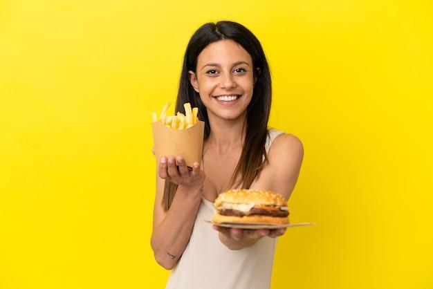 Młoda kaukaska kobieta trzyma burgera i frytki na żółtym tle