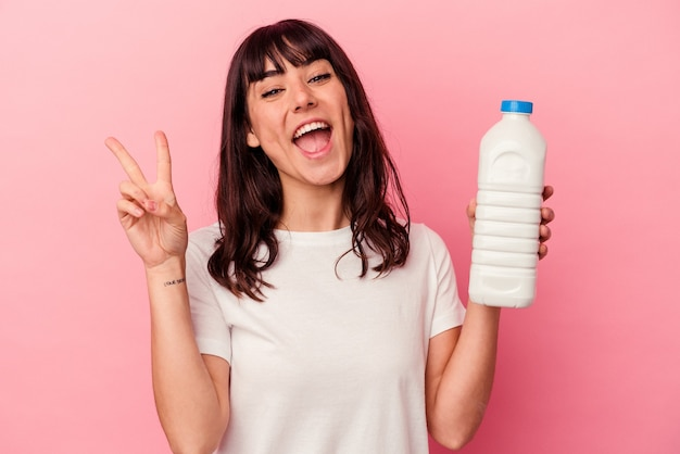Młoda kaukaska kobieta trzyma butelkę mleka na białym tle na różowym tle radosna i beztroska pokazująca palcami symbol pokoju.