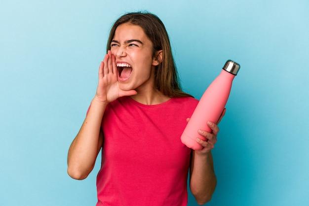 Młoda kaukaska kobieta trzyma butelkę wody na białym tle na niebieskim tle krzycząc i trzymając dłoń w pobliżu otwartych ust.