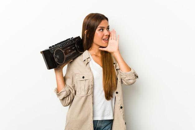 Młoda kaukaska kobieta trzyma guetto blaster krzycząc i trzymając dłoń w pobliżu otwartych ust.