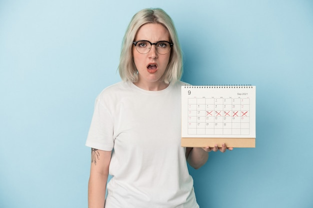 Młoda kaukaska kobieta trzyma kalendarz na białym tle na niebieskim tle krzycząc bardzo zły i agresywny.