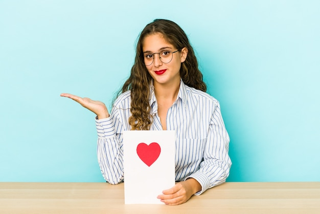 Młoda kaukaska kobieta trzyma kartę walentynki na białym tle pokazując miejsce na kopię na dłoni i trzymając drugą rękę na talii.