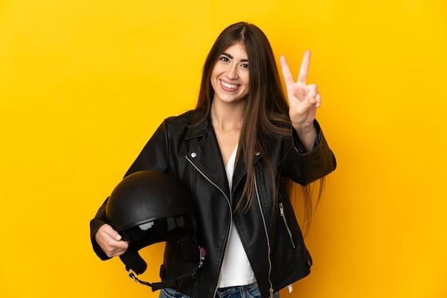 Młoda Kaukaska Kobieta Trzyma Kask Motocyklowy Na Białym Tle Na żółtym Tle, Uśmiechając Się I Pokazując Znak Zwycięstwa Premium Zdjęcia