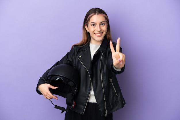 Młoda kaukaska kobieta trzyma kask motocyklowy na białym tle