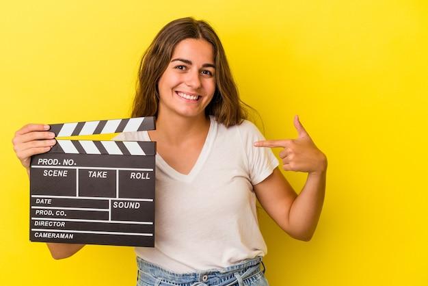 Młoda kaukaska kobieta trzyma klapsę na białym tle na żółtym tle osoba wskazująca ręcznie na miejsce na koszulkę, dumna i pewna siebie
