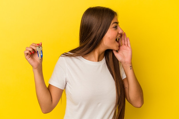 Młoda kaukaska kobieta trzyma klucze do domu na białym tle na żółtym tle krzycząc i trzymając dłoń w pobliżu otwartych ust.