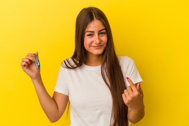 Młoda kaukaska kobieta trzyma klucze do domu na białym tle na żółtym tle, wskazując palcem na ciebie, jakby zapraszając się bliżej.