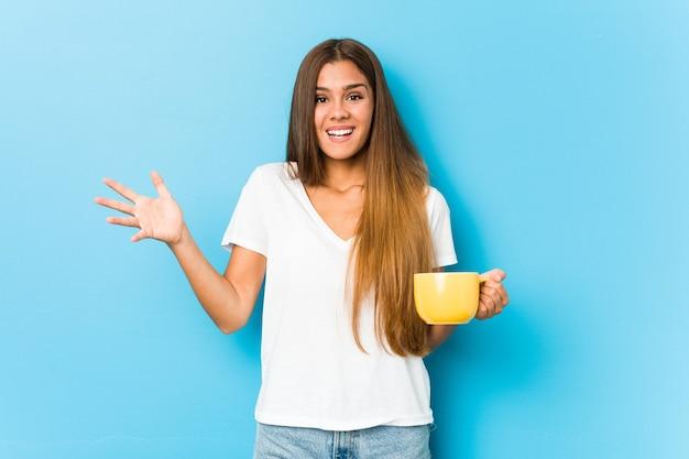 Młoda kaukaska kobieta trzyma kubek kawy odbiera miłą niespodziankę, podekscytowany i podnoszący ręce.