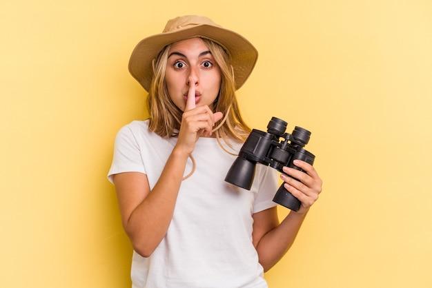 Młoda kaukaska kobieta trzyma lornetkę na białym tle na żółtym tle dochowując tajemnicy lub prosząc o ciszę.