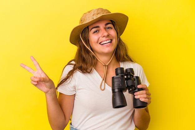 Młoda kaukaska kobieta trzyma lornetkę na białym tle na żółtym tle radosna i beztroska pokazująca palcami symbol pokoju.