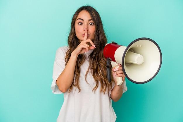 Młoda kaukaska kobieta trzyma megafon na białym tle na niebieskim tle dochowując tajemnicy lub prosząc o ciszę.