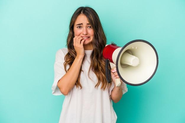 Młoda kaukaska kobieta trzyma megafon na białym tle na niebieskim tle gryząc paznokcie, nerwowa i bardzo niespokojna.