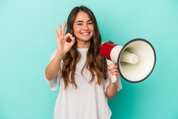 Młoda kaukaska kobieta trzyma megafon na białym tle na niebieskim tle wesoły i pewny siebie pokazując ok gest.