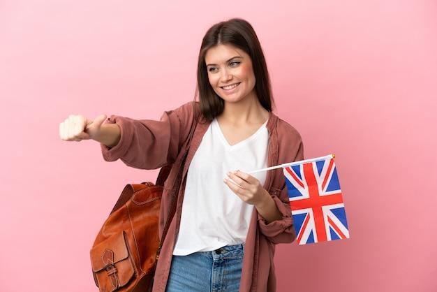 Młoda kaukaska kobieta trzyma na białym tle flagę wielkiej brytanii, dając gest kciuka w górę