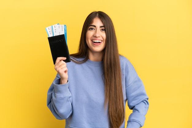 Młoda kaukaska kobieta trzyma paszport na białym tle na żółtym tle z niespodzianką wyrazem twarzy facial