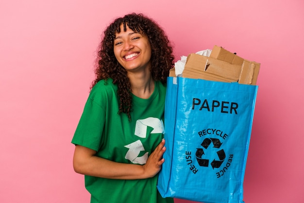 Młoda kaukaska kobieta trzyma plastik z recyklingu na białym tle na różowym tle śmiejąc się i bawiąc.