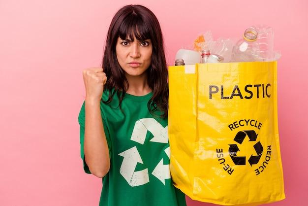 Młoda kaukaska kobieta trzyma plastikową torbę z recyklingu na białym tle na różowym tle pokazując pięść do kamery, agresywny wyraz twarzy.
