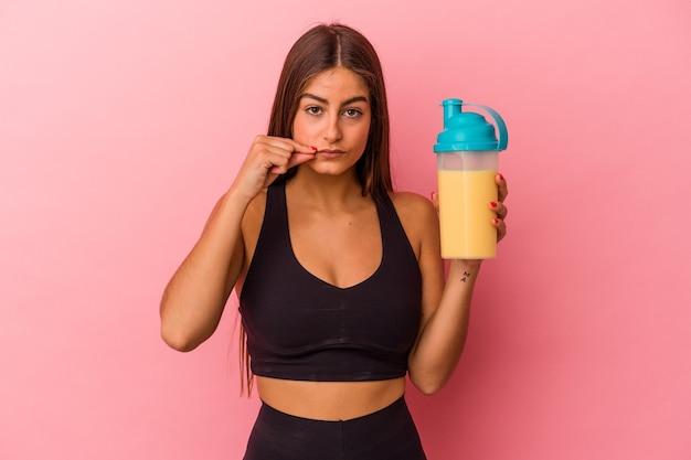 Młoda kaukaska kobieta trzyma shake proteinowy na białym tle na żółtym tle z palcami na ustach dochowując tajemnicy.