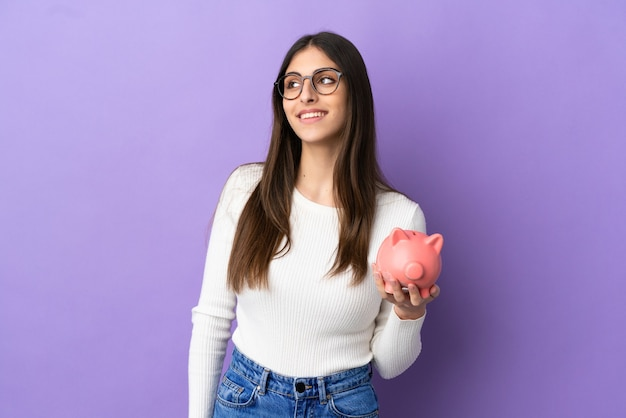 Młoda kaukaska kobieta trzyma skarbonkę odizolowaną na fioletowym tle, myśląc o pomyśle, patrząc w górę