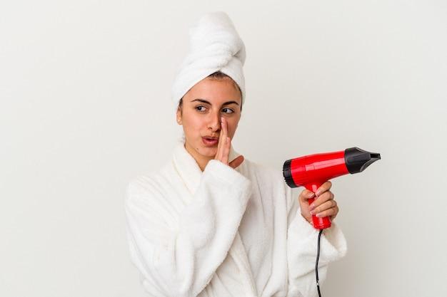 Młoda kaukaska kobieta trzyma suszarkę do włosów na białym tle mówi tajne wiadomości o gorącym hamowaniu i patrząc na bok