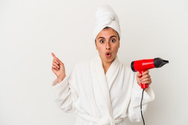 Młoda kaukaska kobieta trzyma suszarkę do włosów na białym tle, wskazując na bok